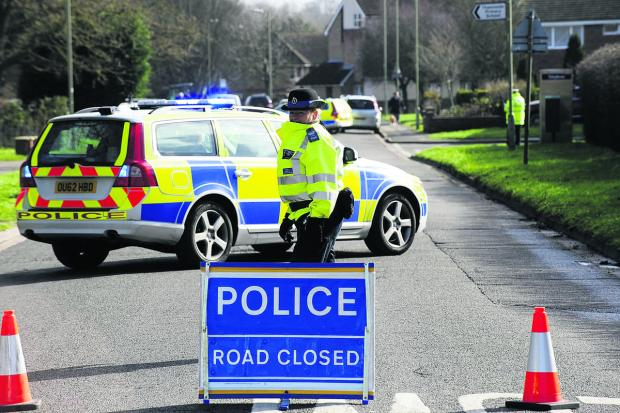 Police officers close Preston Road, Abingdon, after a cyclist died following a collision with a car at the Kennington Close junction