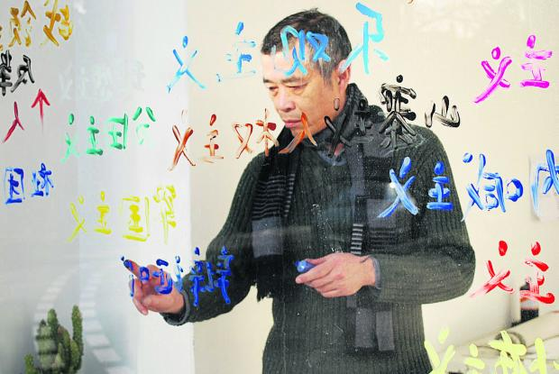 Cai Yuan paints a window as part of the Optimism exhibition