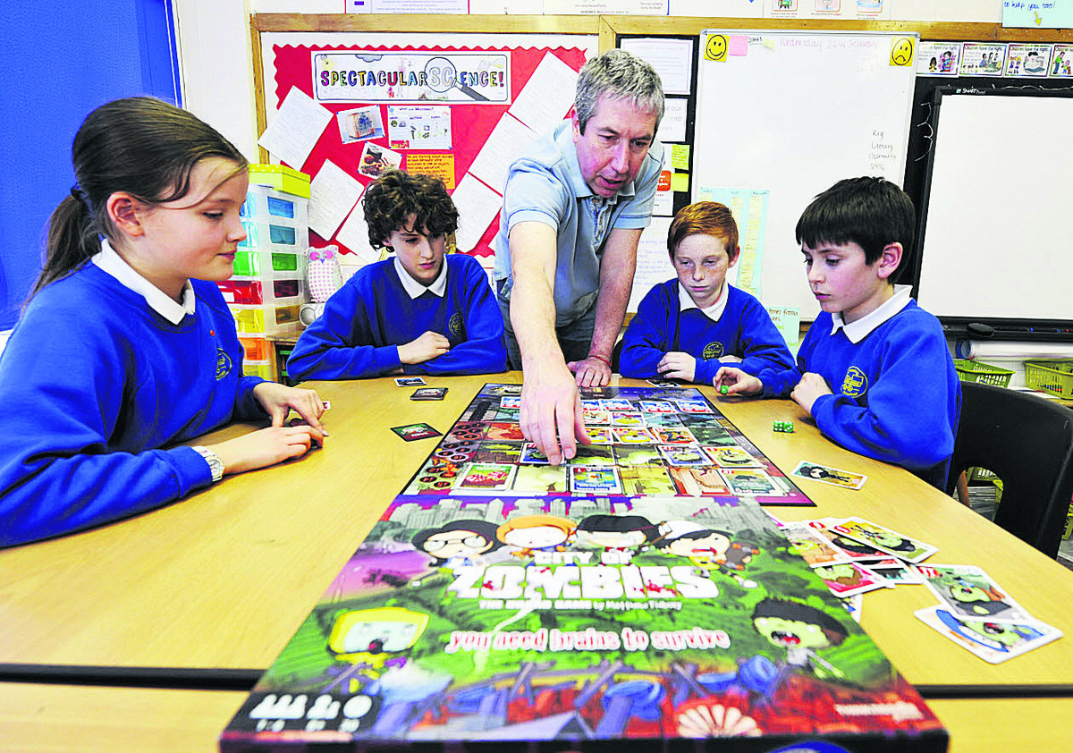 City of Zombies creator Matt Tidbury playing the game with Didcot's Manor Primary School pupils, from left, Tara Allinson, 11, Alfie Baum, 1