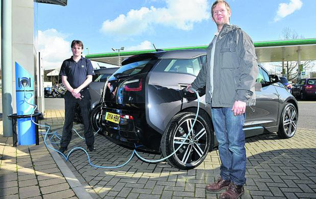 John Ganderton, right, with his new BMW electric car wit