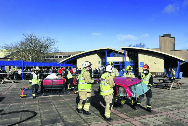 The Oxford Times: Firefighters move the roof out of the way after cutting it from the wrecked car to free the trapped 'casualty'