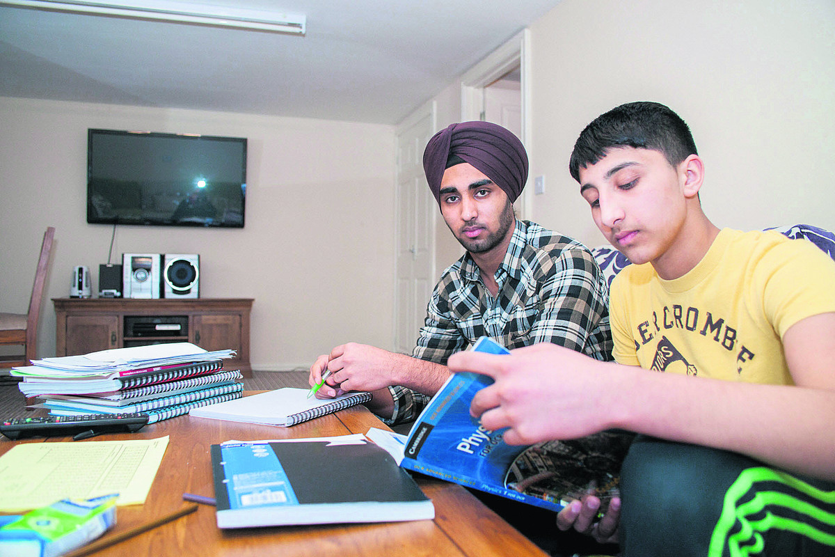 Karan Turna, 17, and Jugraj Turna, 13, doing schoolwork in the study-cum-gym at the bottom of their garden in Dene Road Headington
