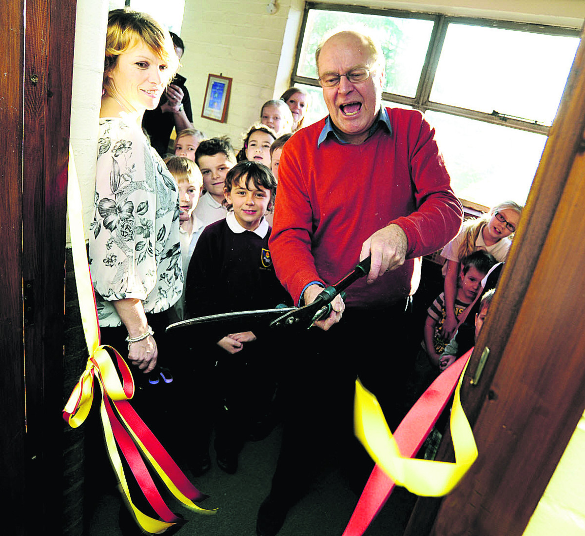 Korky Paul cuts the ribbon to open the library watched by volunteer librarian and revamp co-organiser Kathy Webb and some of the children