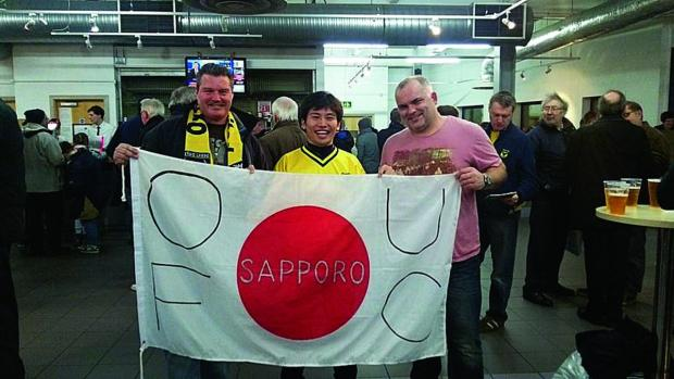Jez Allen, Kotaro Sumita and Neil Warland at the Kassam Stadium. Mr Sumita made the flag himself and he was given a tour of the stadium before the game against Cheltenham Town