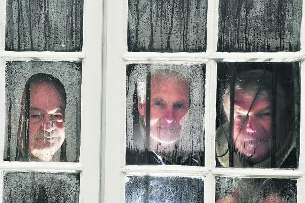 The Oxford Times: From left, West Oxford Bowls Club committee member Mick Pinfold, member Cyril Honour and president Mick Alderson peer out through the bar windows in the clubhouse through condensation caused by the floods