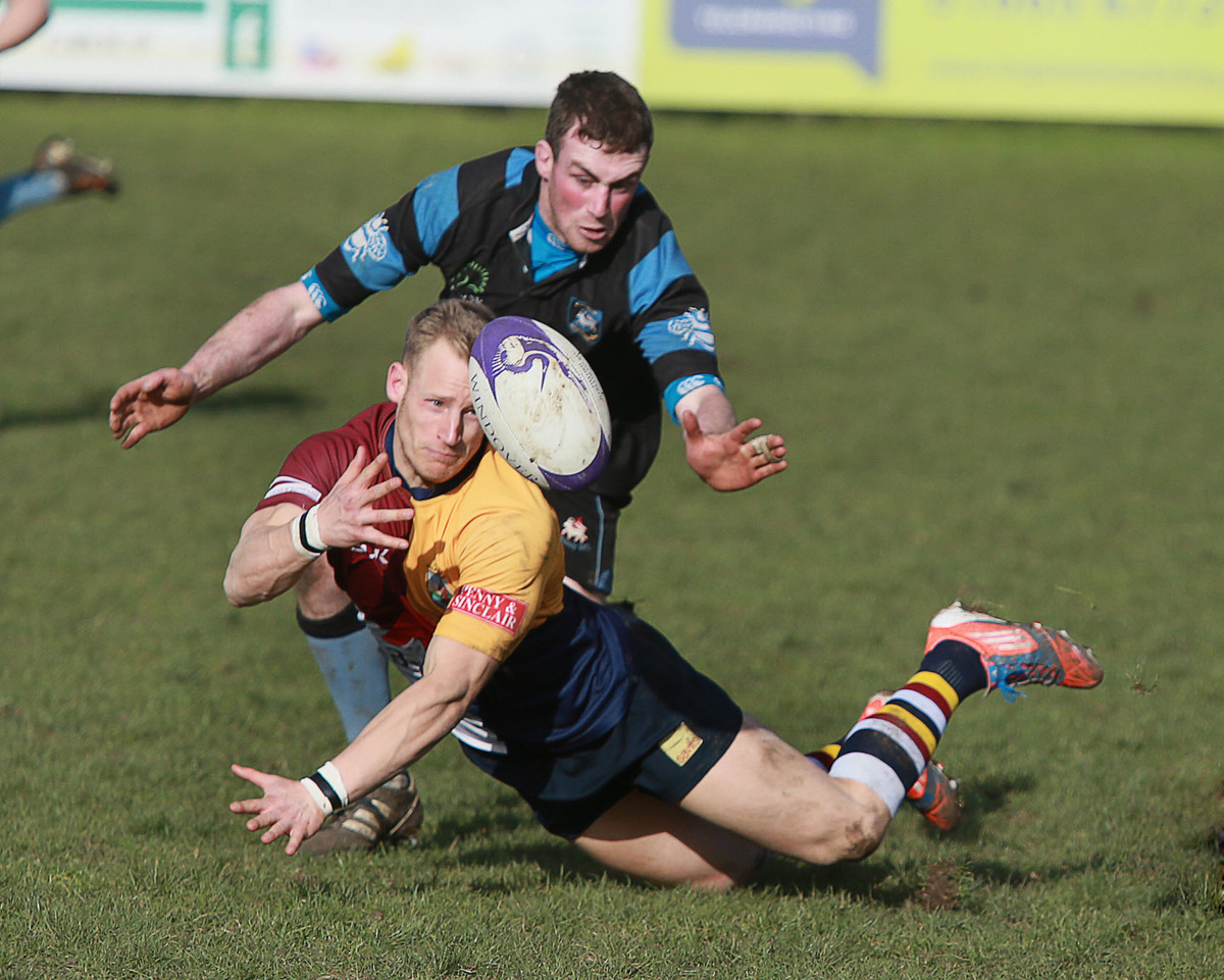 Oxford Harlequins' Jack Robinson gets his pass away as Witney's Carl Campbell closes in