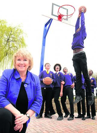 Oxford Spires headteacher Sue Croft with Nelvin Air slam dunking on the new basketball courts