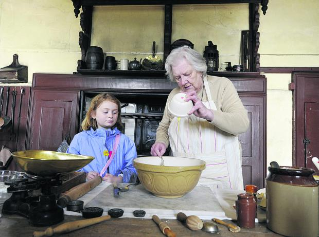 Elizabeth Moulder gives nine-year-old Jasmine Walker a baking lesson