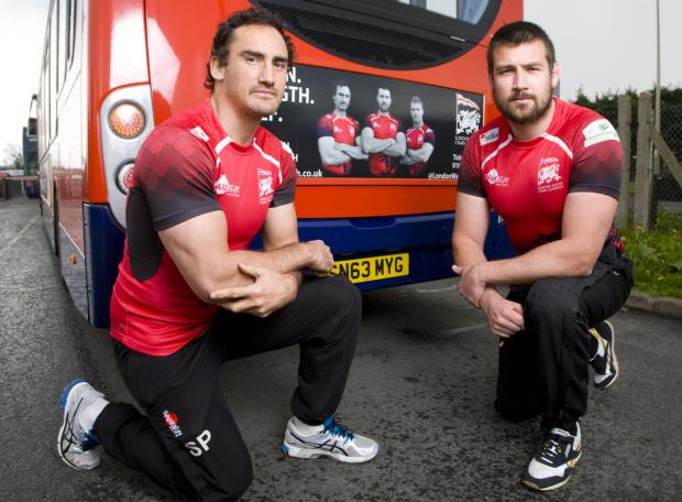 Sonny Parker (left) and club captain Matt Corker, who returns from a heart problem tomorrow, pose alongside their faces on the London Welsh's advert which also features Tom May