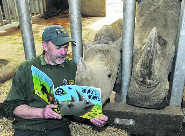 Senior keeper lan Pringle reads to Astrid the white rhino calf and her mother Nancy