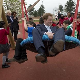 The Oxford Times: Mayor of London Boris Johnson watches Prince Harry on a swing with local school children at the new Queen Elizabeth Olympic Park in Stratford, east London
