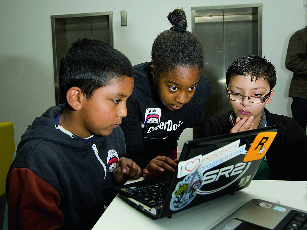 Tyriah Allison, centre, helps Mokbool Amin and Jilani Amin with coding at the Coder Dojo workshop                                     Picture:  OX66267 Antony Moore