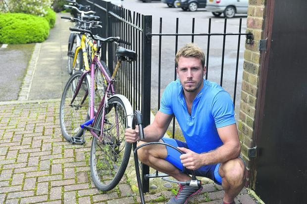 Daniel Smith holds the bicycle locks that were cut by thieves