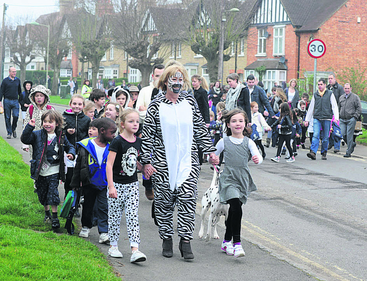 Headteacher Lisa Rowe and Poppy Ellis, six, left, and Verity Bennett, seven, lead the way as the walking bus crosses the road