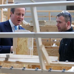 The Oxford Times: Prime Minister David Cameron talks to frame assembler Darren Jones during a visit to Westbridge Furniture Ltd, a sofa manufacturers in Greenfield, North Wales
