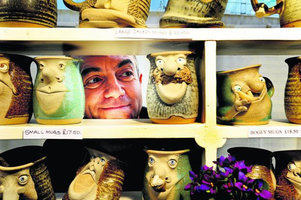 The Oxford Times: Richard Cave's shortlisted picture of Sean Keefe, of Muggins pottery, peering through his mugs at a Living Crafts for Christmas shopping event at Blenheim Palace
