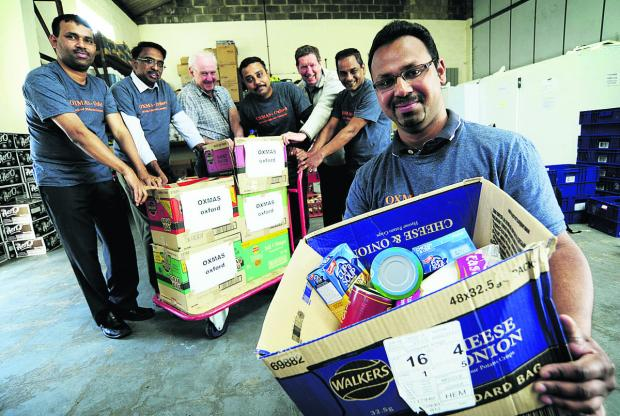 David Cairns, third left, co-founder and chairman of the Oxford Food Bank, and Cllr Roy Darke, third right, with members of the Malayalee Samajam, from left, Roopesh John, Rajan Philip, Joby Joseph, George Kutty and