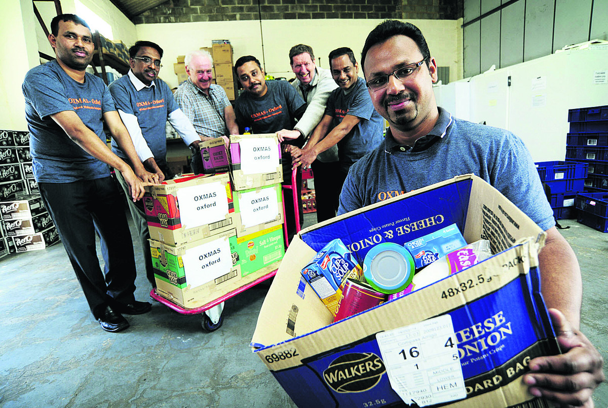 David Cairns, third left, co-founder and chairman of the Oxford Food Bank, and Cllr Roy Darke, third right, with members of the Malayalee Samajam, from left, Roopesh John, Rajan Philip, Joby Joseph, George Kutty and Jobil Skaria.   Picture: OX66616 David