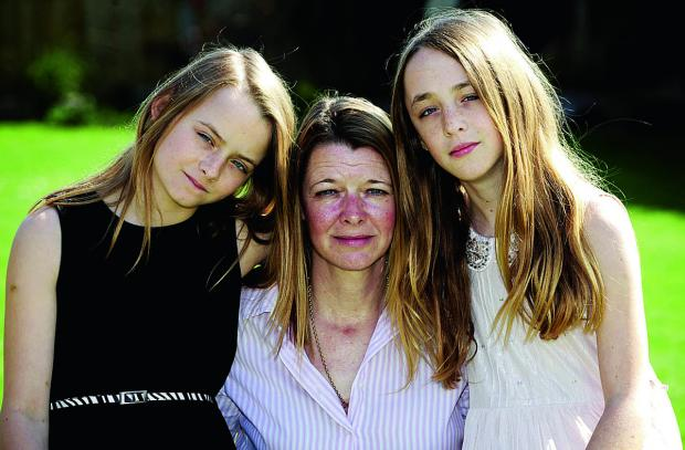 Mum Sharon Barney with twins Kerri, left, and Holly, 11, who are upset at having to attend separate schools. Picture: OX66495 David Fleming