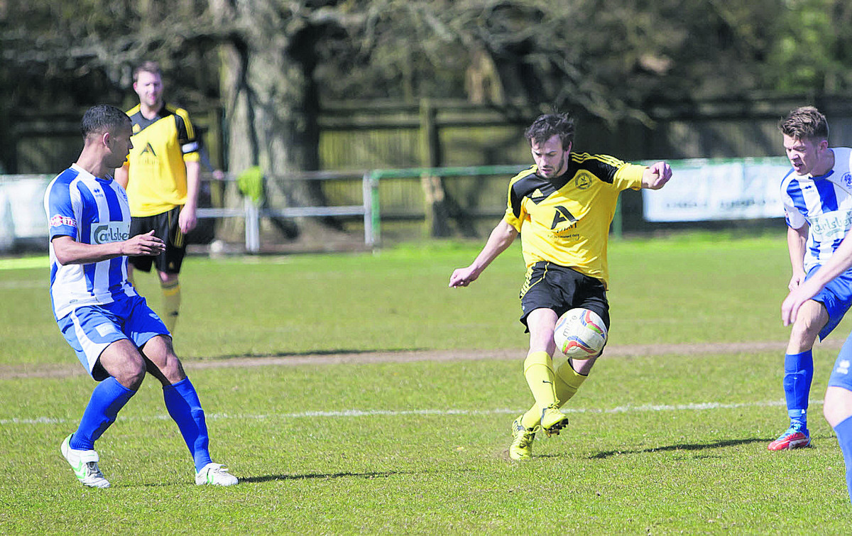 North Leigh's Mark Bell gets between two Clevedon defenders to shoot for goal on Saturday
