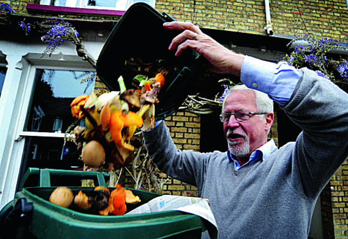 Cllr John Tanner empties his food waste into his food caddy, ready for collection