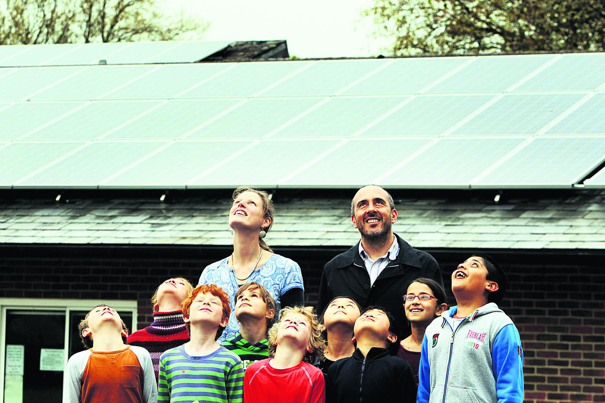 Als Parker, back left, and Adriano Figueiredo, back right, with pupils at St Barnabus School, Oxford, which has already had solar panels fitted