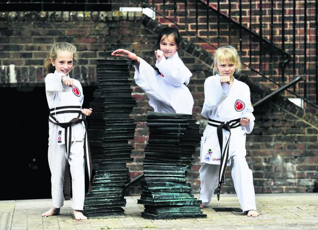 From left, Lara Plested, eight, Chloe Wood, nine, and Alisha Pitts, 10 show off their martial arts skills