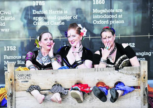 The Oxford Times: Kaleidoscope dance group members from left, Kay White, Louise Hilling and Philippa Watts taking a break from performing to try out the Oxford Castle stocks