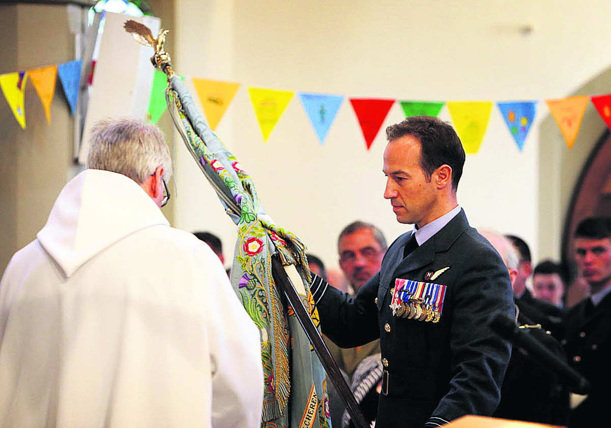 Wing Commander Mark Biggadike places the old standard on the altar