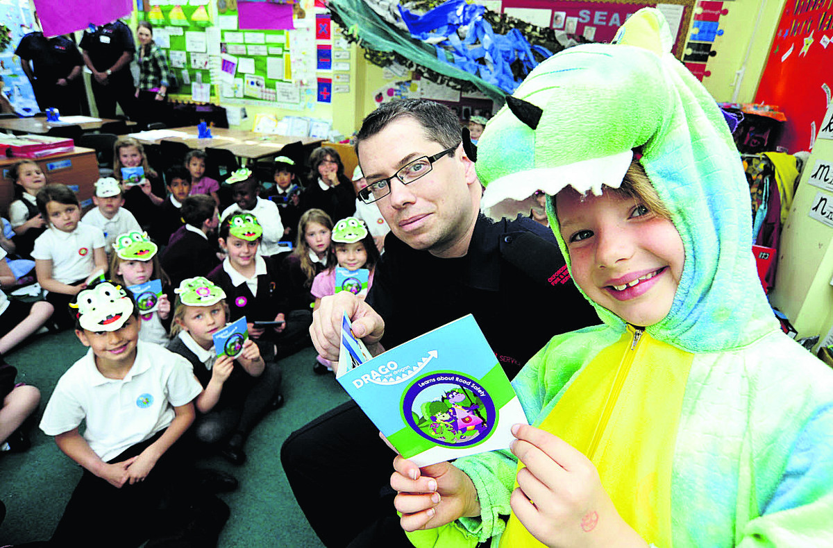 Firefighter William Savage reads the new book to Maisie Babic, seven, and her class at Edward Feild Primary Schoo