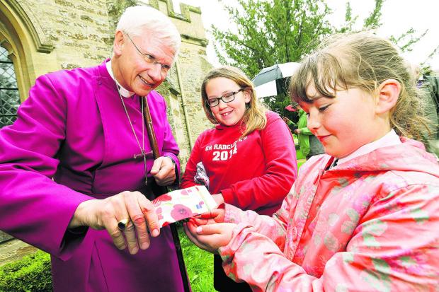 The Oxford Times: The Bishop of Dorchester, the Rt Rev Colin Fletcher, helps Dr Radcliffe's CofE Primary School pupils Charlotte Scrivens, 11, left, and Tilly Hancock, eight, plant poppy seeds at St Peter & St Paul Church, Steeple Aston.  Picture: OX66926 Damian Halliwel