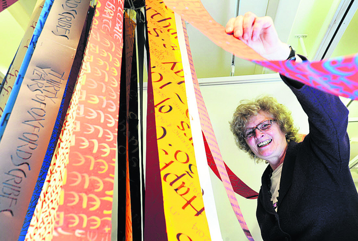 Cynthia Harper with a maypole with calligraphy ri