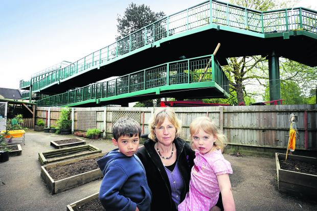Childfirst manager Andrea Leonard, with Harry Saxton, four, and Sophie Walton, three, with the railway footbridge which has shadowed their outdoor play area. Picture : OX67047 Damian Halliwell