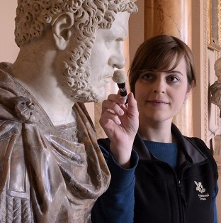 Tabatha Donaldson, a NT Conservation Cleaner at Wimpole Hall in Cambridgeshire as she cleans a Roman bust of Caracalla