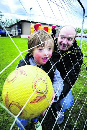 Back of the net: Archie Cunningham, four, enjoys the football fun with family friend Gerard Bell