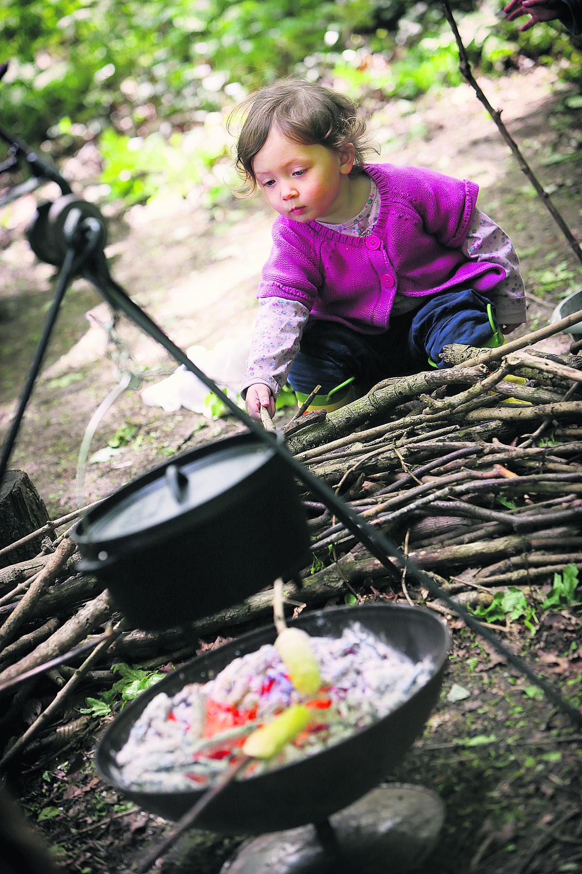 Anabelle Kinghan, two, waits as her bread cooks on a stick over the fire