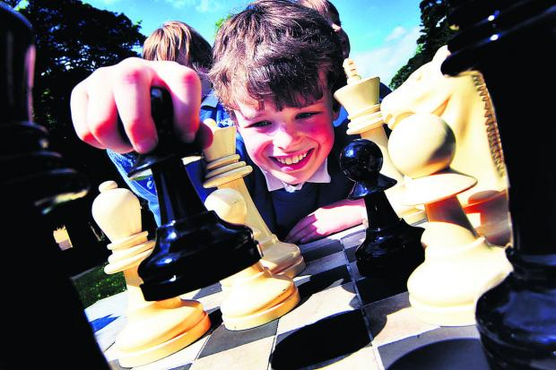 Thomas Chapman, nine, makes his move at the new chess table in Bury Knowle Park