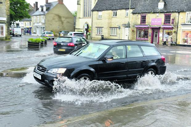A car negotiates the floods in Welch Way, Witney, yesterday. Picture: Denis Kennedy