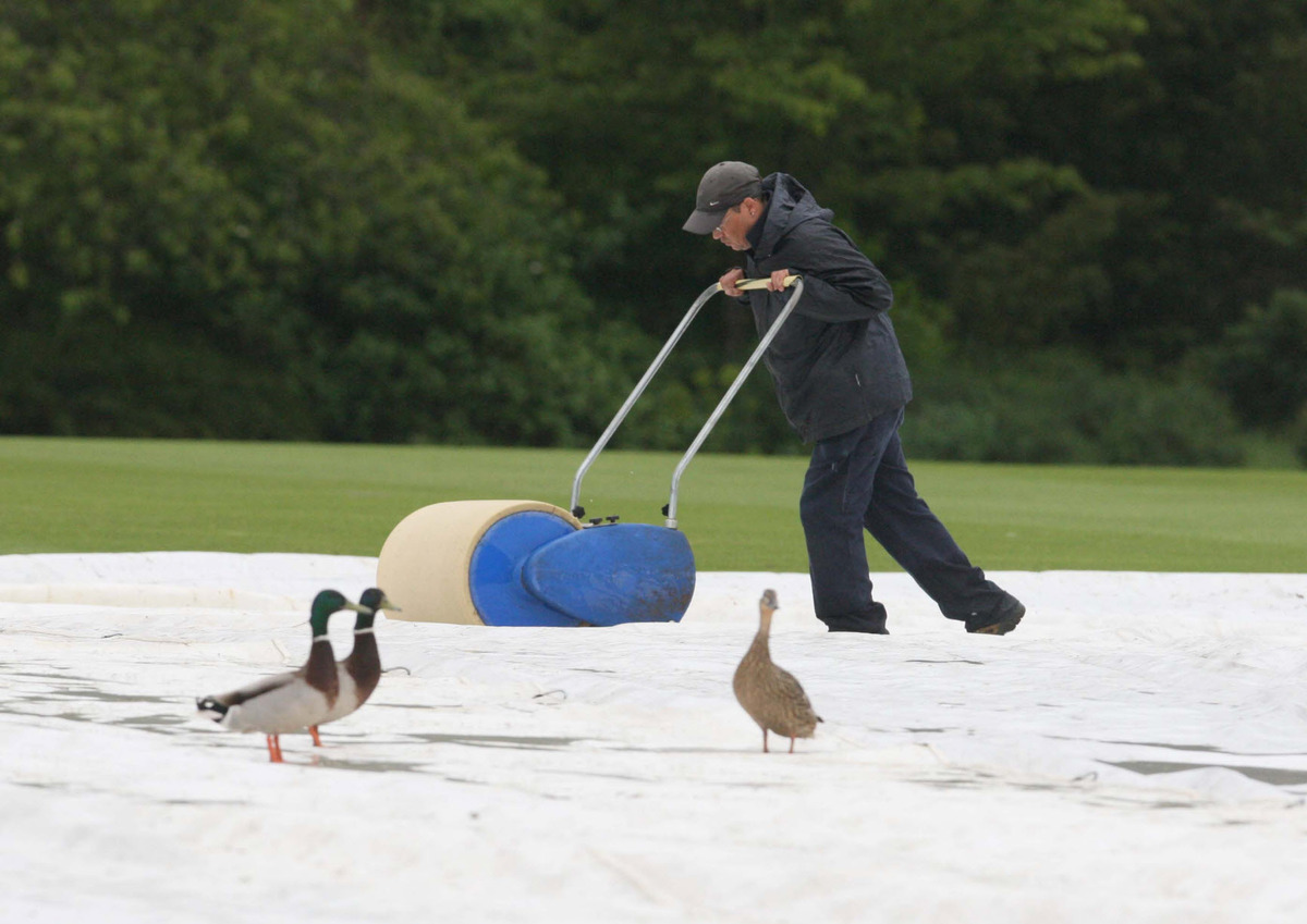 Three ducks look on as a groundsman tries in vain to get The Parks ready for last Friday's abandoned Varsity Twenty20