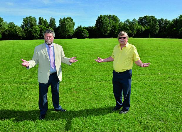 The Oxford Times: Disappointed Banbury and District Show organisers Colin Clarke, left, chairman of the show committee, and Mike Hall, town council recreation amenities manager, at the sodden Spiceball Park	    Picture: OX67726 Simon Williams
