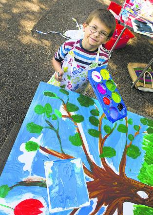 Eight-year-old Jerrid Gamage works on the mural. Inset: Artist Lizzy McBain with Bella Skaer, six