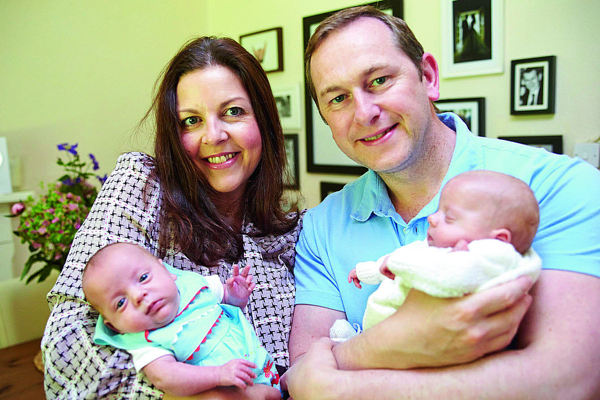 Julie and Drew Brown hold their 14-week-old twin daughters Beaux, left, and Scarlett, right, at their home. The couple are doing an abseil to raise money for the hospital that saved their daughters, who were born at just 26 weeks     Picture: OX67729