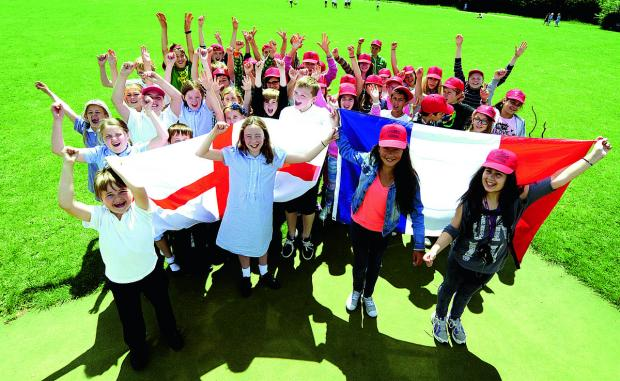 Front, from left, with flags are Ladygrove pupils Peter Yeates, 10, and Molly Sexton, 10, and French twin town school visitors Coline Santiago, 10, and Alexandra Reverbel, 10, with the pupils from schools in Didcot and Meylan, France   Picture: OX67783