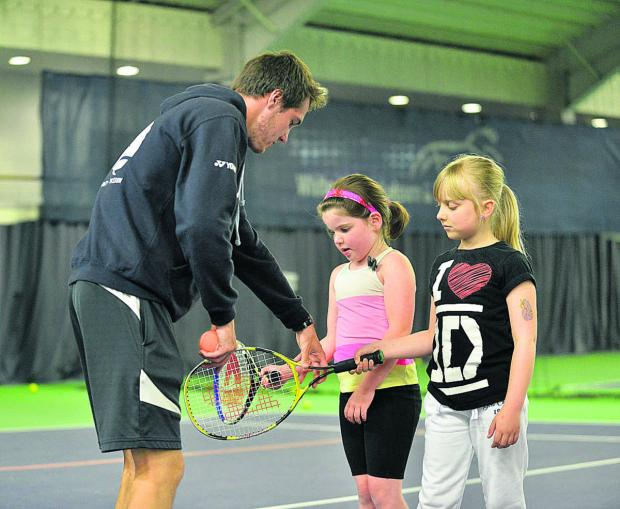 Coach Josh Dawson shows Ruby Edwards (pink top) and Grace Vanstone the basics
