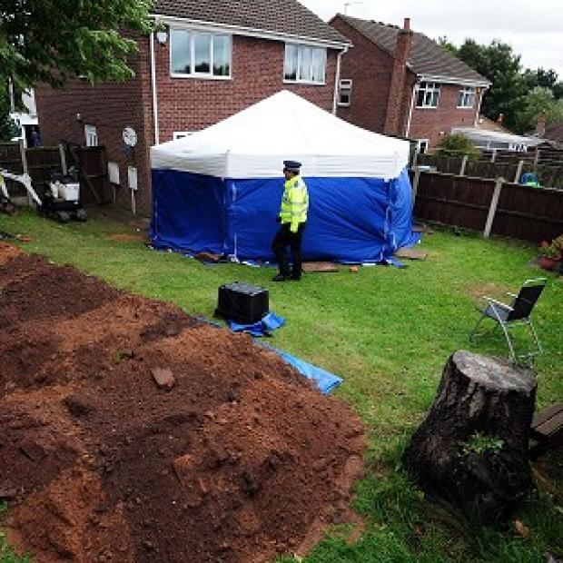 The Oxford Times: Police in the garden of a house in Mansfield, where the remains of William and Patricia Wycherley were discovered