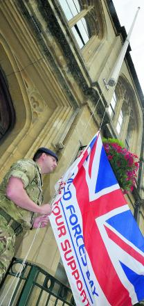 A Lance Corporal from the Army Reserves raises a Union Flag outside Banbury Town Hall for Armed Forces Day. Picture: OX68009 Simon Williams