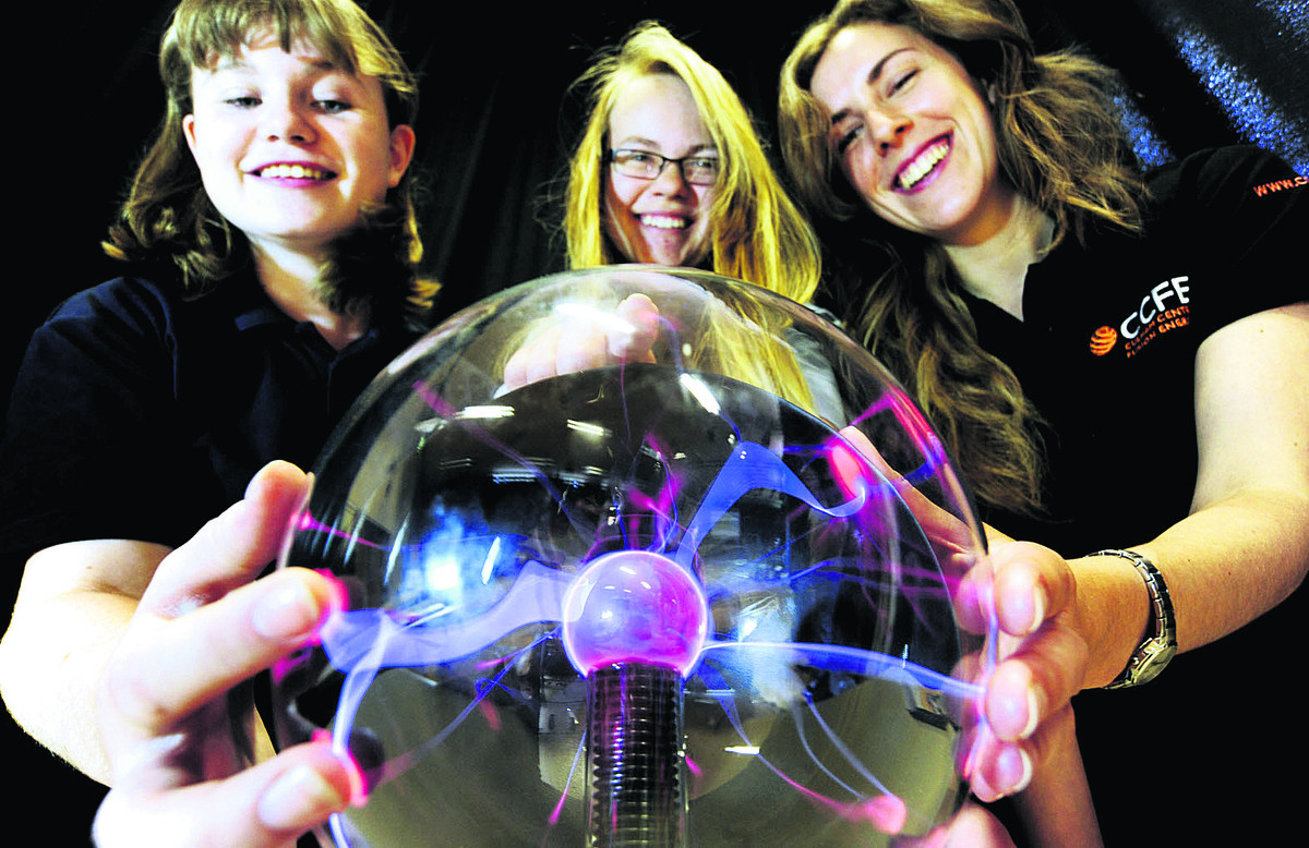 Bright sparks: From left, Didcot Girls' School pupils Sarah Tammadge-Wall, 14, and Tiffany Taylor, 15, with Alex Cackett, a physicist from the Culham Centre for Fusion Energy, try out a static electricity lamp