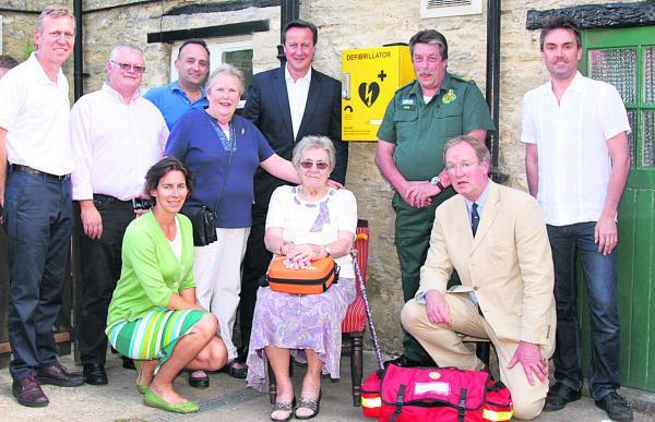The Oxford Times: Prime Minister David Cameron and Dick Tracey, next to the defibillator box, with Hailer residents and GP Dr Robin Carr, front, right