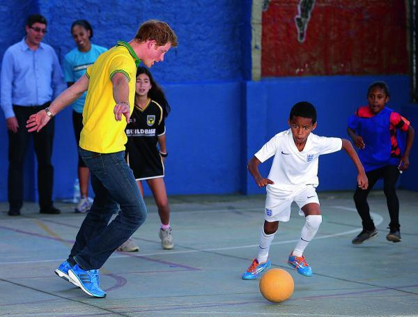 Prince Harry plays football at the ACER Charity for disadvantaged children in Sao Paulo, Brazil. He is watched by a fellow player wearing an old-style Oxford United shirt.             Picture: Chris Jackson/ Getty Images
