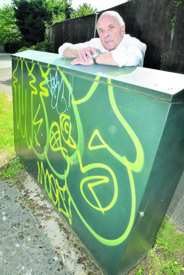 The Oxford Times: Cumnor Parish Council chairman Brian Stops with graffiti on the corner of Arnolds Way and Cumnor Hill. Picture: OX68409 Simon Williams